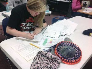 Katie Saint working on a cap and letter for her buddy.